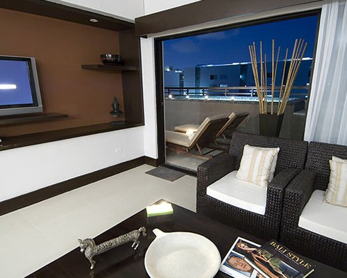 A well furnished living room with a television and balcony with chaise lounge chairs.