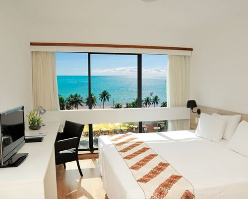 A well furnished bedroom with king bed television and ocean view.