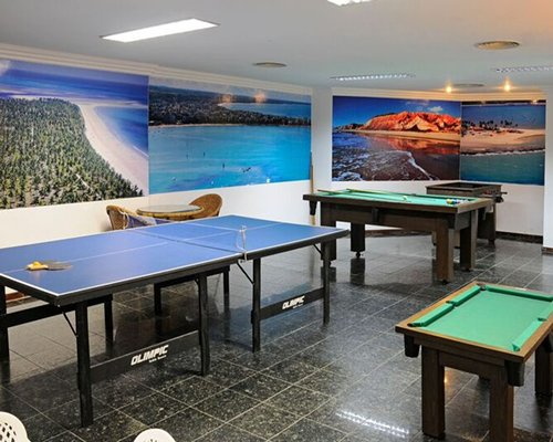 Indoor recreation room with ping pong and pool tables.