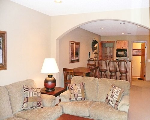 A well furnished living room with open plan kitchen breakfast bar and dining area.