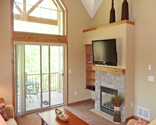 A well furnished living room with a television fireplace and balcony with patio furniture.