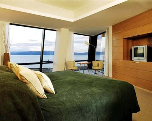 A well furnished bedroom with a queen bed television dining area and waterfront view.