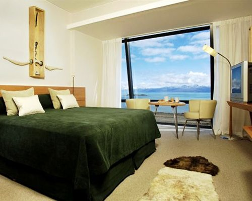 A well furnished bedroom with a television and the water view.