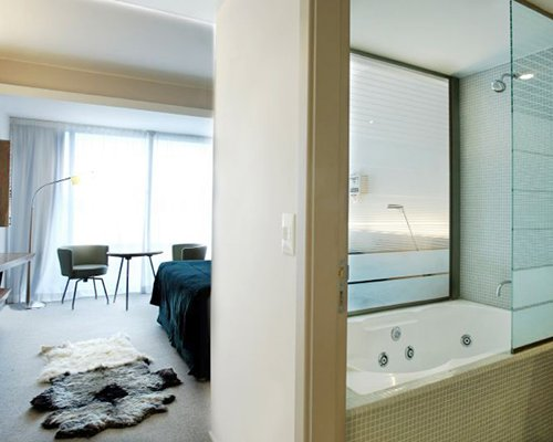 A well furnished bedroom with attached bathroom having bathtub and shower.