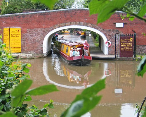 A view of canal boat under the bridge surrounded by wooded area.