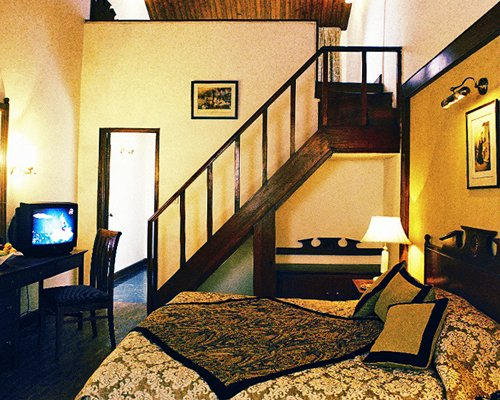 A well furnished bedroom with a television and wooden stairway.