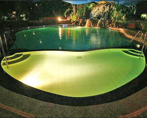 An outdoor grotto pool at night.