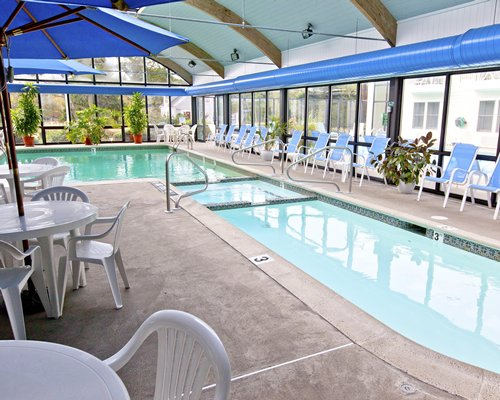 Indoor swimming pool with chaise lounge chairs patio furniture and sunshades.