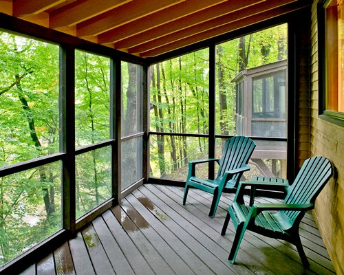 Balcony with patio chairs and view of a wooded area.