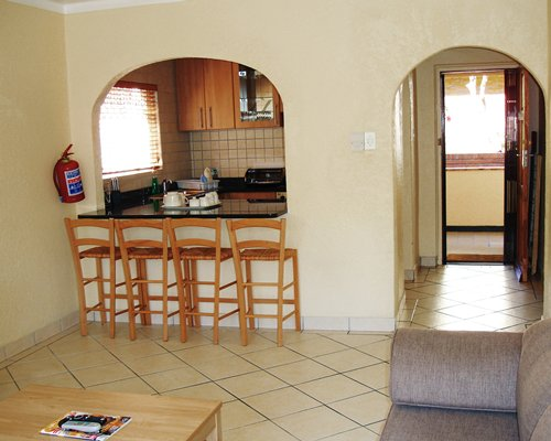 A furnished living area alongside the kitchen with a breakfast bar.