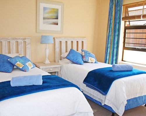 A well furnished bedroom with two twin beds and an outside view.