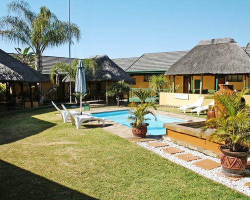 Scenic exterior view of Ukuthula Lodge with outdoor swimming pool chaise lounge chairs and sunshade.