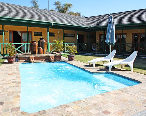 Outdoor swimming pool with chaise lounge chairs and sunshade alongside a unit at Ukuthula Lodge.