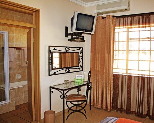 A room with a television alongside bathroom with bathtub.