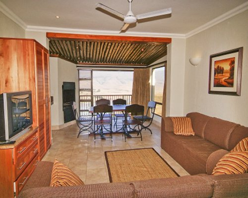 A well furnished living room with television dining area and outdoor view.