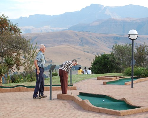 View of people playing in a miniature golf alongside a picnic area and the mountains.