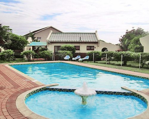 An outdoor swimming pool with water fountain.