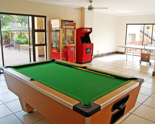 An indoor recreation room with ping pong pool table and arcade game.