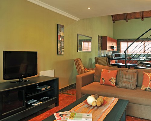 A well furnished living room with a sofa television and kitchen area.