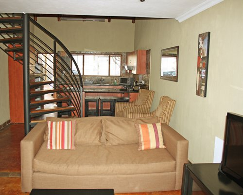 A well furnished living room with television open plan kitchen breakfast bar and spiral stairway.