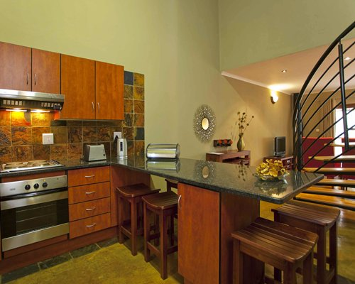 A well equipped kitchen with a breakfast bar alongside the living area with a television and a staircase.