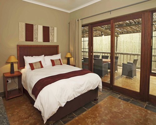 A well furnished bedroom with patio furniture in the balcony.