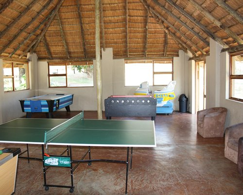 An indoor recreation room with ping pong air hockey and table soccer.