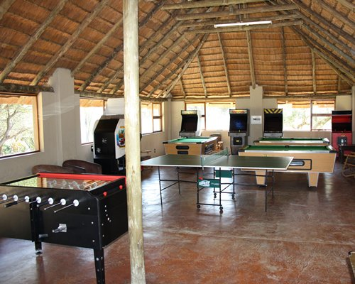 An indoor recreational room with pool table ping pong scorer table and arcade games.