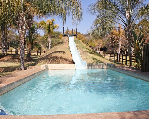 Outdoor swimming pool with a water slide.