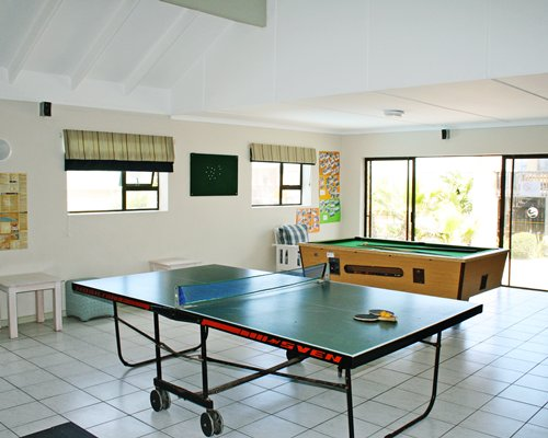 An indoor recreational room with pool table and ping pong.