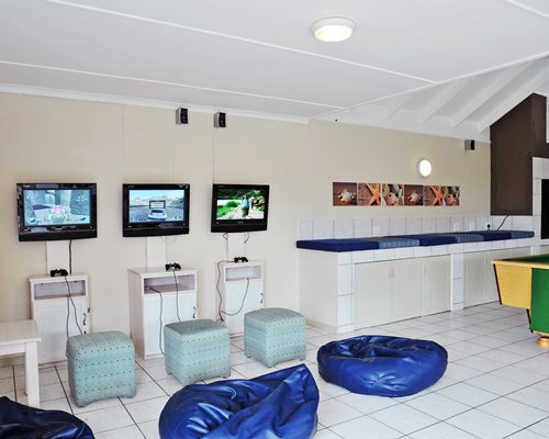 An indoor recreational room with video games and pool table.