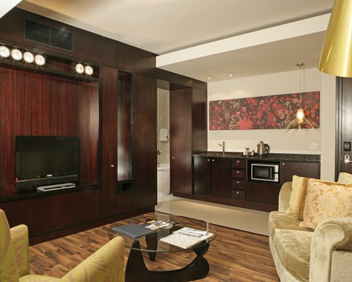 An open plan living room with television and kitchen.