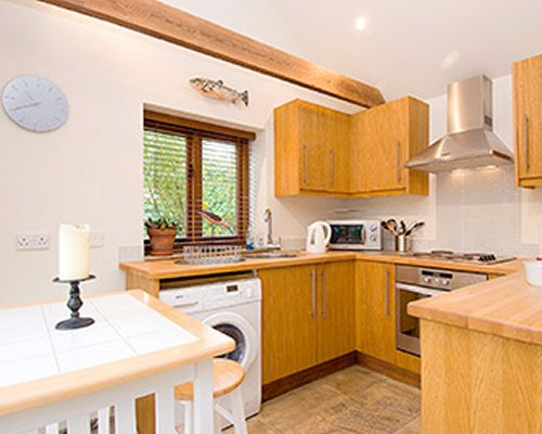 An open plan kitchen with dining area and outside view.