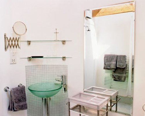 A bathroom with stand up shower and single sink.
