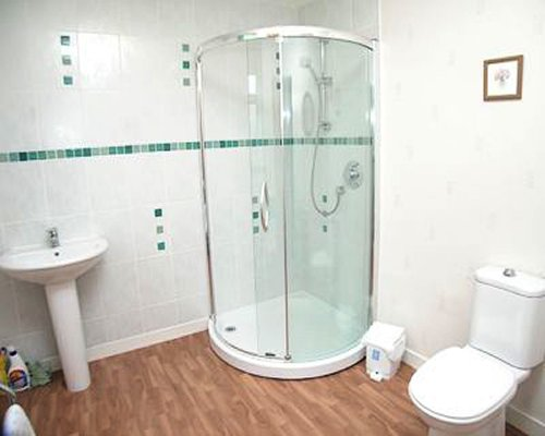 A bathroom with a shower stall and single sink.