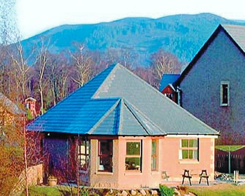 Exterior view of a unit at The Bungalow with wooded area alongside the mountains.