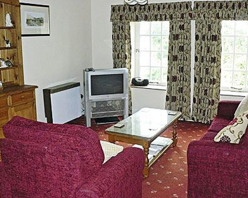 A well furnished living room with a television sofas and an outside view.