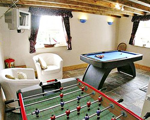 An indoor recreational area with pool table and foosball.