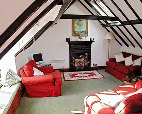 A well furnished living room with television and fireplace in the vaulted ceiling.