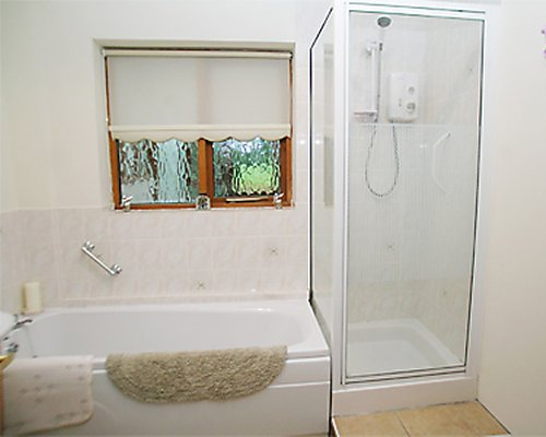 A bathroom with bathtub and stand up shower.