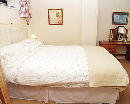 A well furnished bedroom with double bed and dresser.