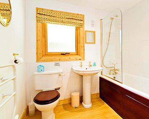 A bathroom with a bathtub shower and single sink vanity.