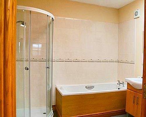 A bathroom with bathtub shower and a single sink.