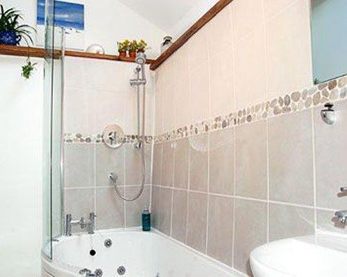 A bathroom with shower bathtub and sink.