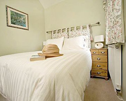 A well furnished bedroom with hat and book on the bed.