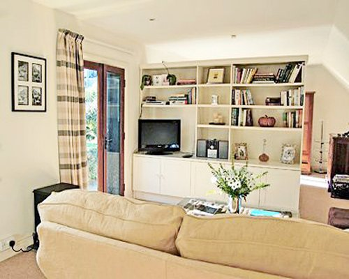 A well furnished living room with television bookshelf and outdoor view.