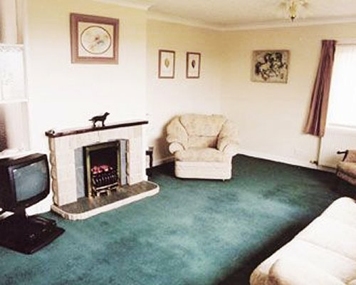 A well furnished living room with television a fire in the fireplace and outside view.