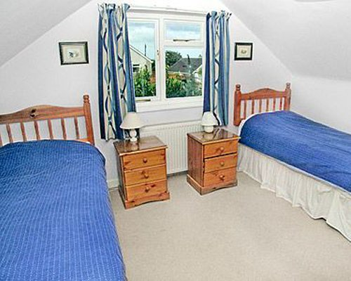 A well furnished bedroom with twin beds and outside view.