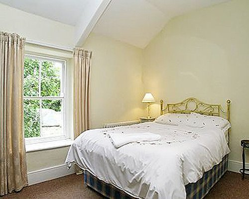 A well furnished bedroom with a double bed and outside view.