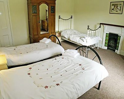 A well furnished bedroom with two twin beds and a single bed.